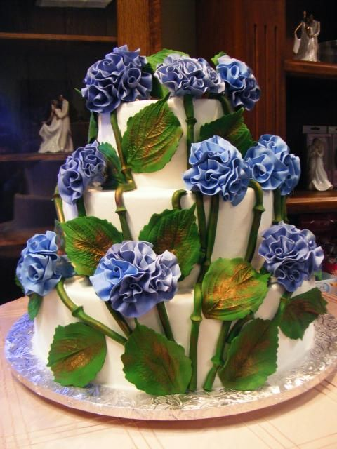 Large clusters of blue-rolled chocolate hydrangea ruffles with green leaves brushed in copper and stems. By Konditor Meister Elegant Wedding Cakes.
