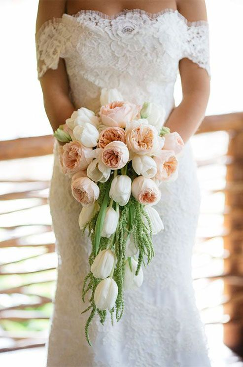 Soft peach ranunculus and crisp white tulips cascade from this bride's beautiful bouquet. Spring  Tulip Inspiration. Photo by Stephen Karlisch