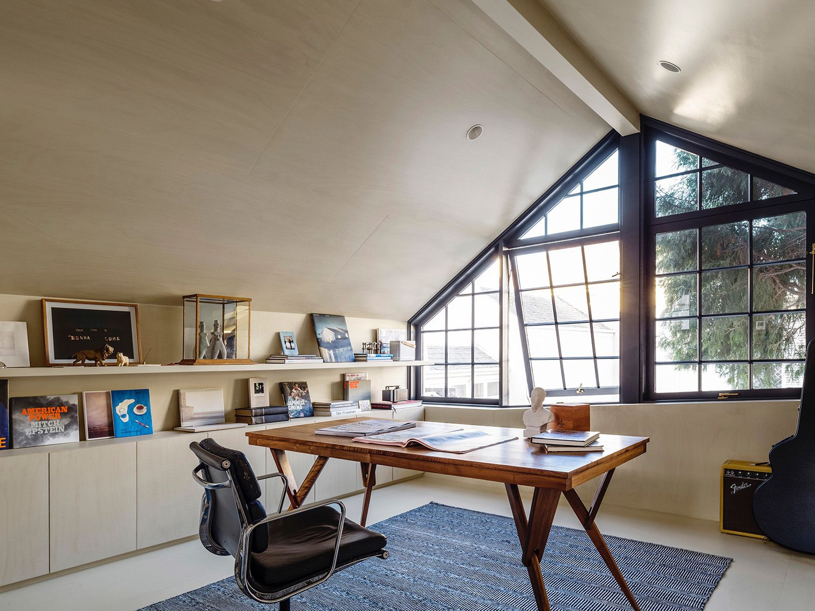The study space over the garage is conceived as a cave for a modern man, with walls lined in limed hoop pine boards with matching bookshelf and flooring. © Justin Alexander