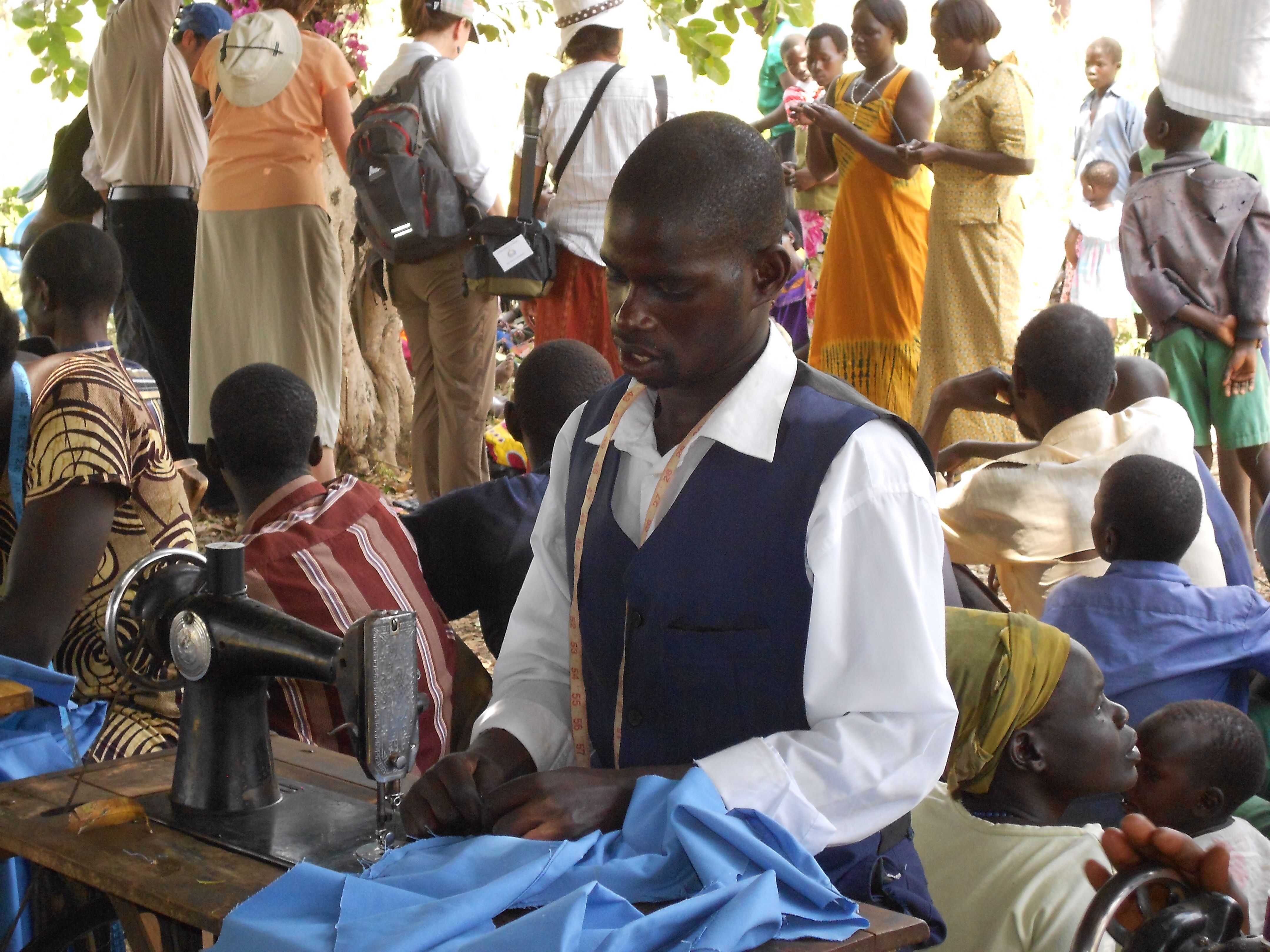 In Uganda....Handsome tailor, doing alterations, under a mango tree.