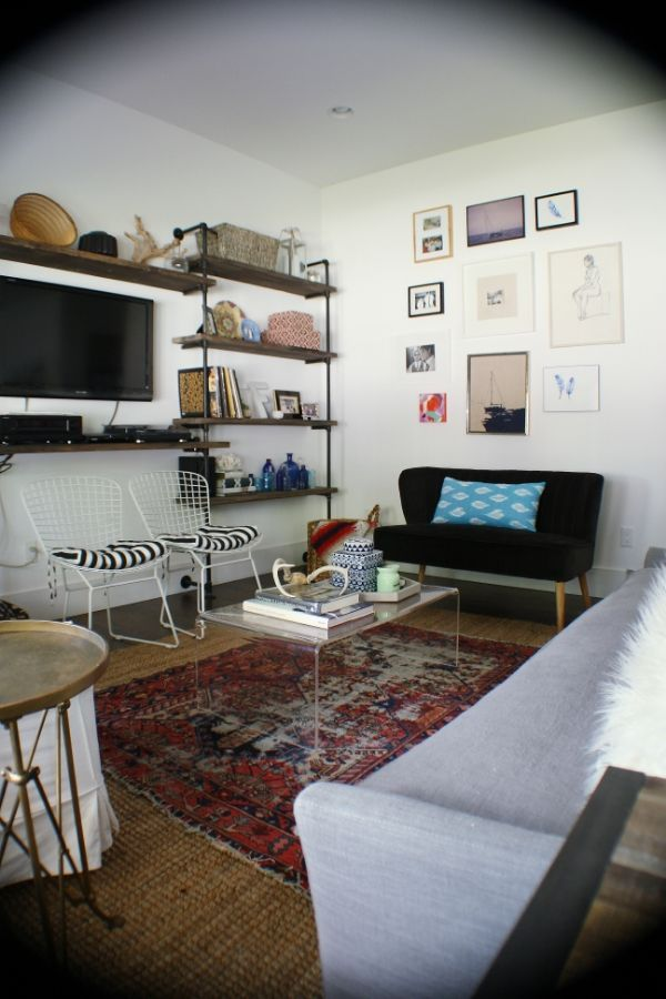 layered jute, persian rugs with wall shelves and white furniture and gallery wall