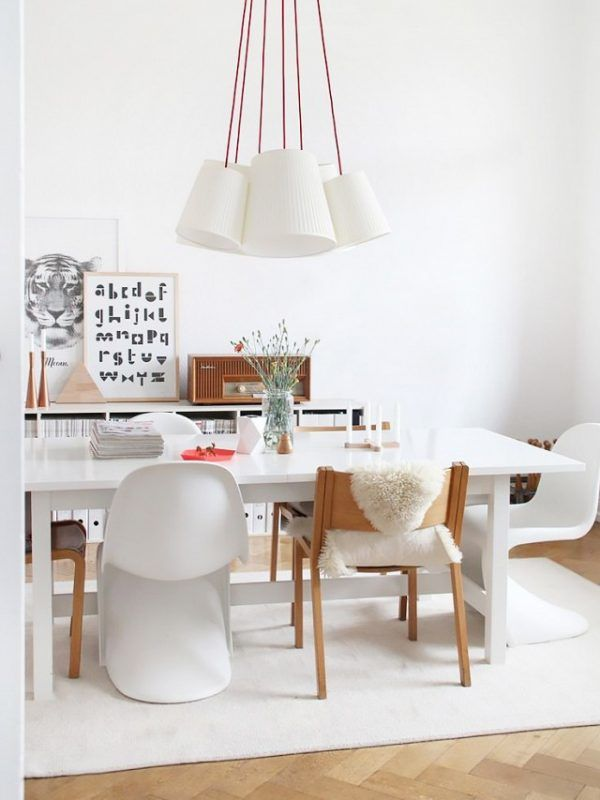 Extraordinary dining room with over-sized pendant light, large white dining table and framed art