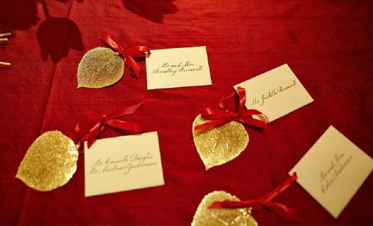 Gold escort cards on a red linen. Perfect for the holidays! Photo by: Robert Wagner.