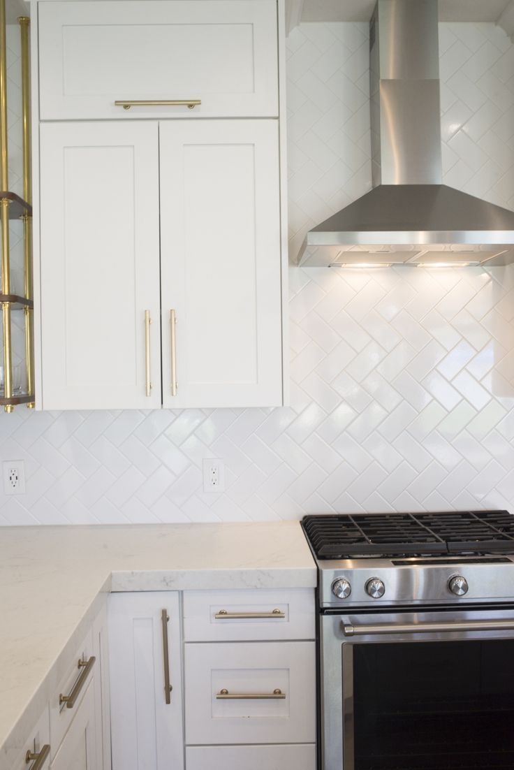 White kitchen with gold hardware white subway tile backsplash and white countertops the cabinets