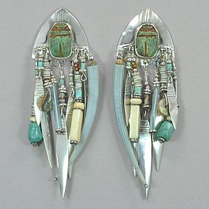 Sterling silver Tabra vintage earrings set with an Egyptian scarab, and with a variety of beads including shell heishi, green dentalium shell, carabao bone, and turquoise