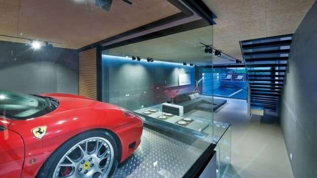 Como si de un escaparate se tratara, el garaje con paredes de cristal da directamente al salón. - Redacción