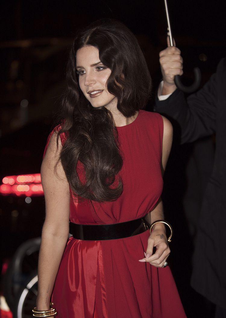 Lana Del Rey Wearing A Red Dress In The Rain On The Red Carpet Long Dark Brown Curled Hair Brown Lipstick Makeup Circa Paradise Era Bea Lana Del Rey Rey Lana [ 1056 x 750 Pixel ]