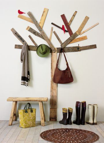 Un portemanteau comme un arbre en planches récupérées collées sur un mur