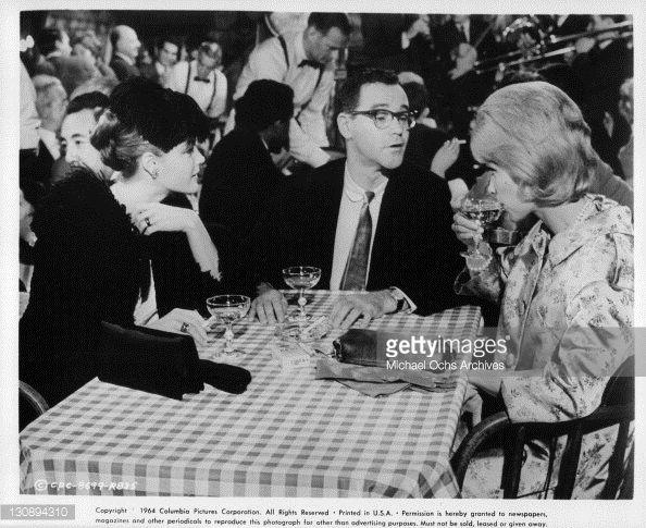 Romy Schneider Jack Lemmon and Dorothy Provine at the table having drinks in a scene from the film 'Good Neighbor Sam' 1964