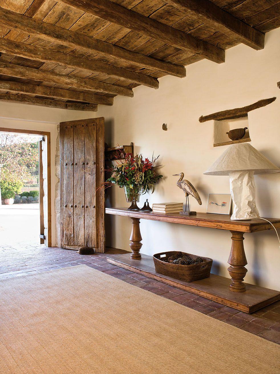 Amplio recibidor con vigas y una alargada mesa con for Detalles decoracion casa