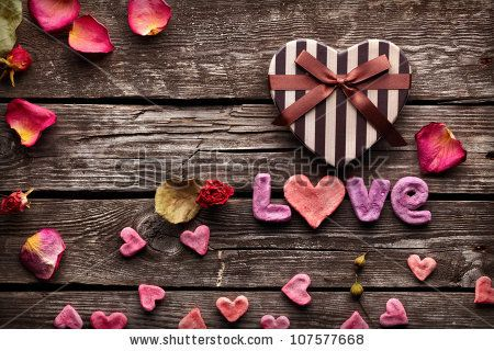 stock photo : Word Love with Heart shaped Valentines Day gift box on old vintage wooden plates. Sweet holiday background with rose petals and small hearts.