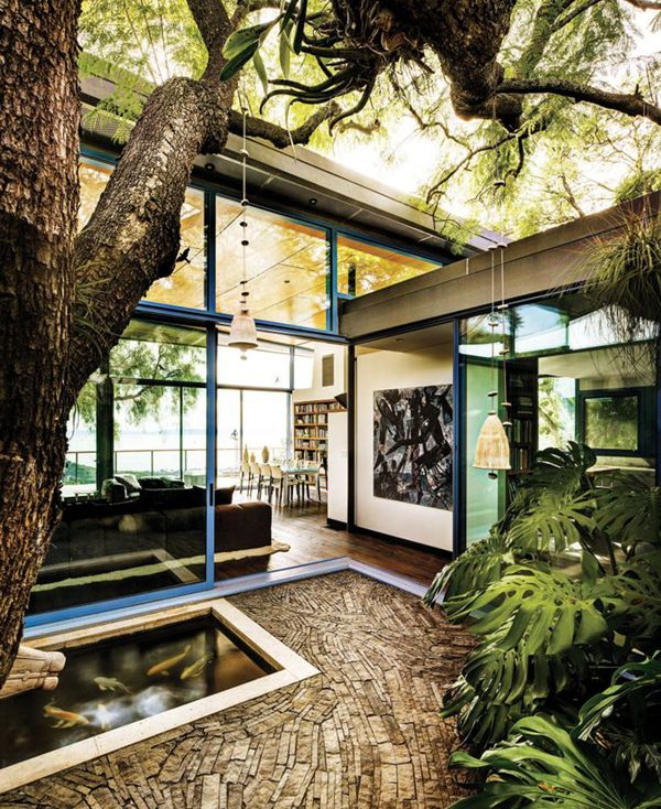 The center atrium deflects natural light to all four corners of the house tropical trees meandering mosaic stone walkways and a koi pond bring the