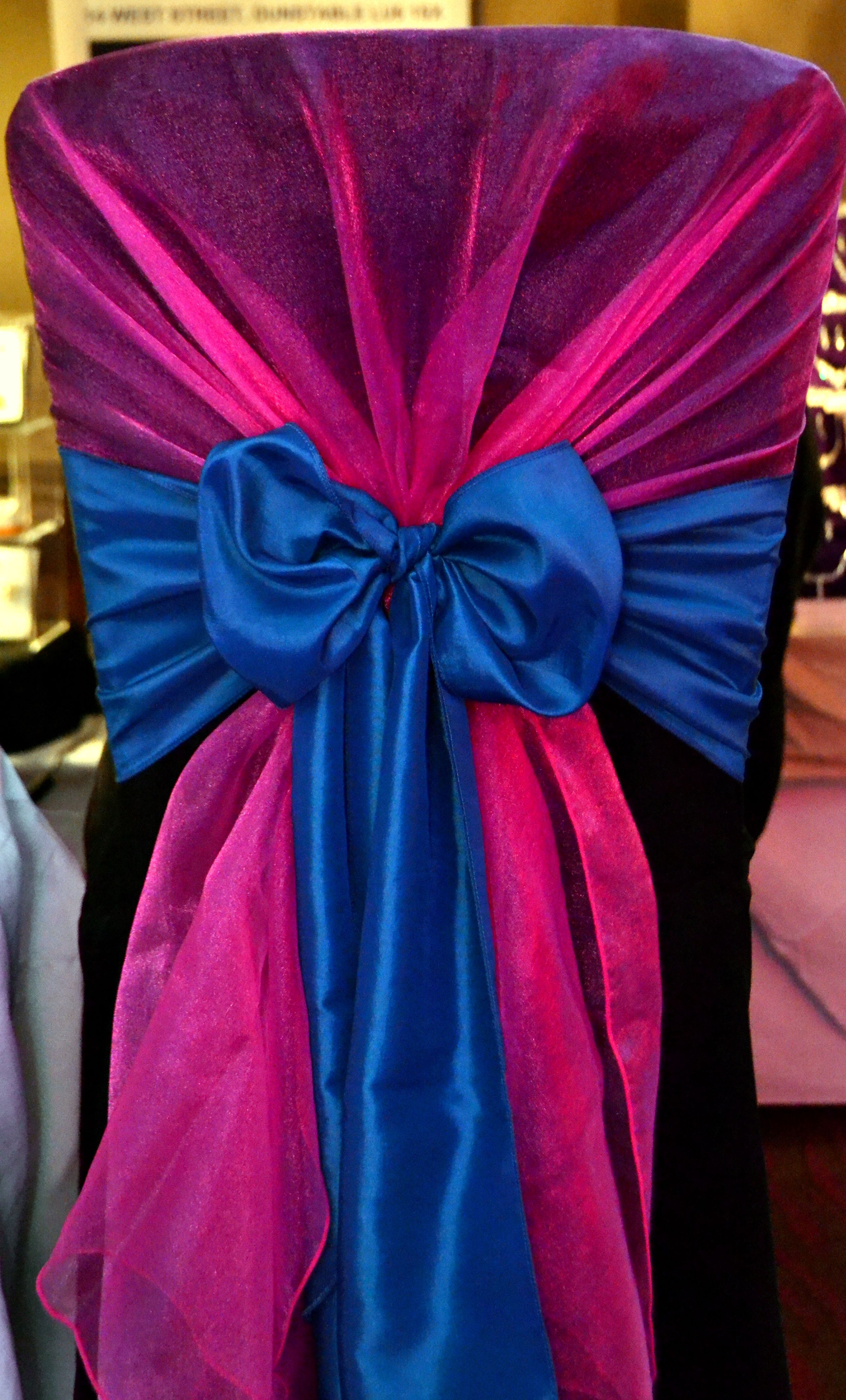 Fuschia pink organz chair shawl with teal satin bow on