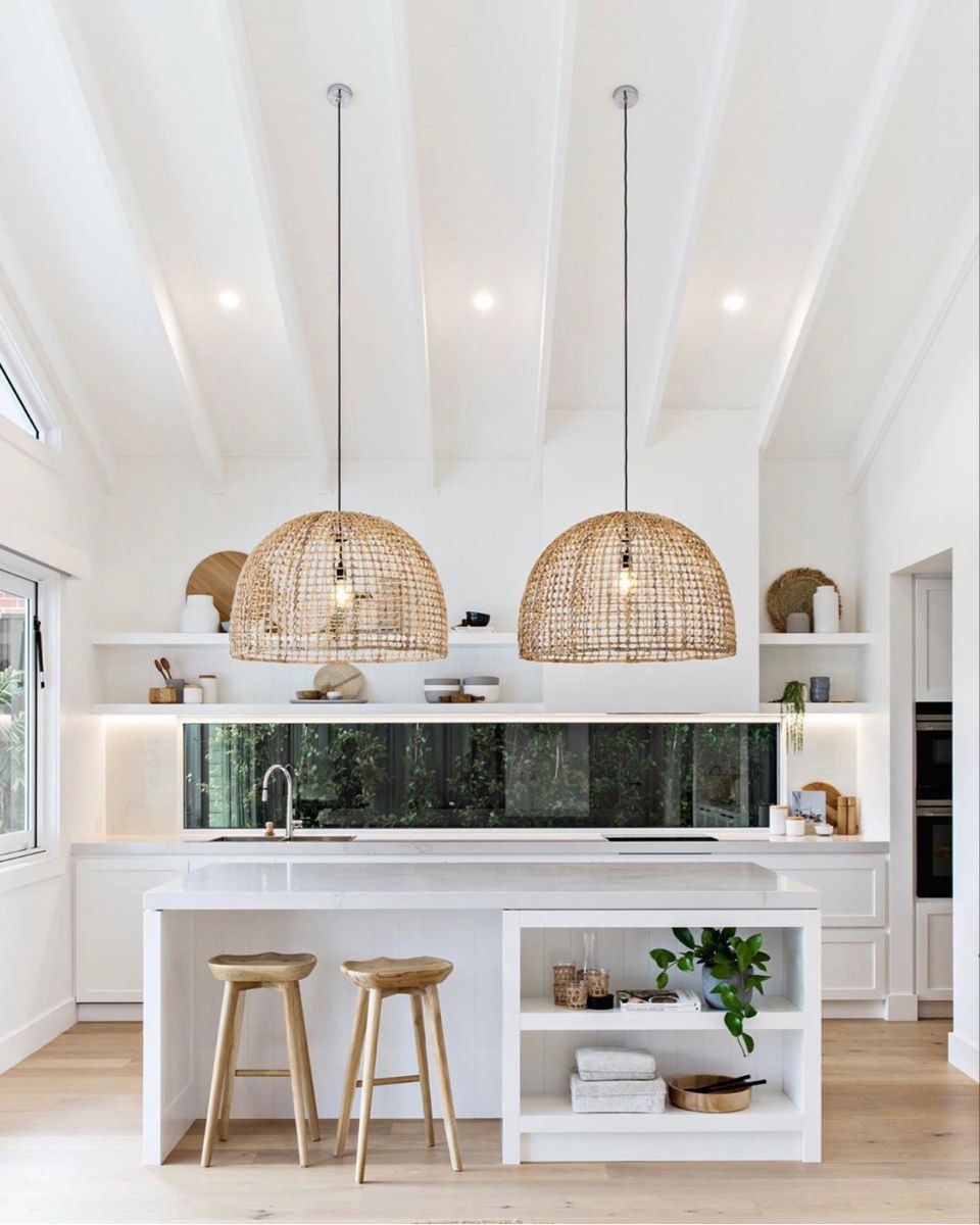 White kitchen with high ceilings and rattan pendants is the