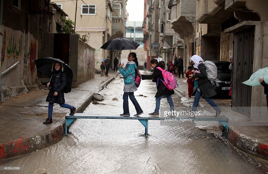 Palestinian kids crossing a bridge conjoining pavements after a rainy day in Gaza City, Gaza on February 19, 2015.