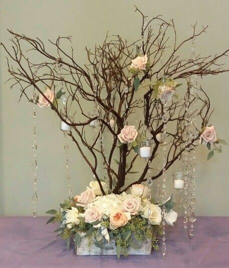 "A whimsical arrangement for a place card table. We attached crystal garland, votives, and roses to the branches. The base of the ""tree"" is full of roses and hydrangeas."