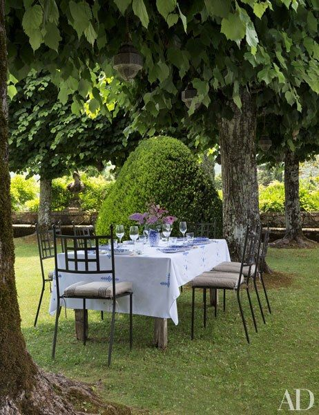 A dining table is set in the shade of linden trees | archdigest.com