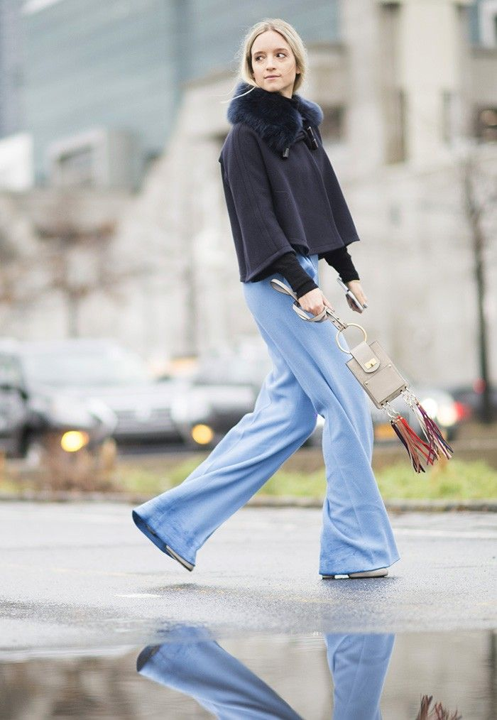 A black cape worn with flared jeans and a Chloé fringed bag