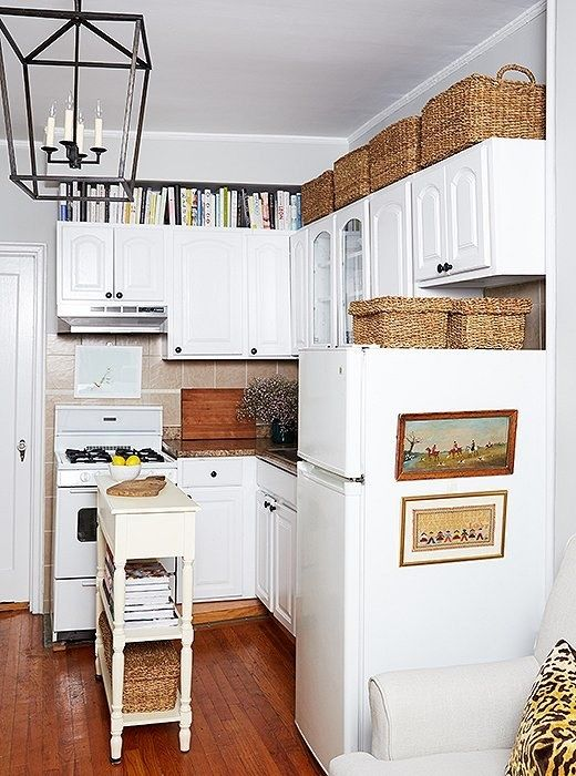 Fill the space above your kitchen cabinets by throwing miscellaneous overflow into neutral storage baskets — they'll totally disguise the clutter.
