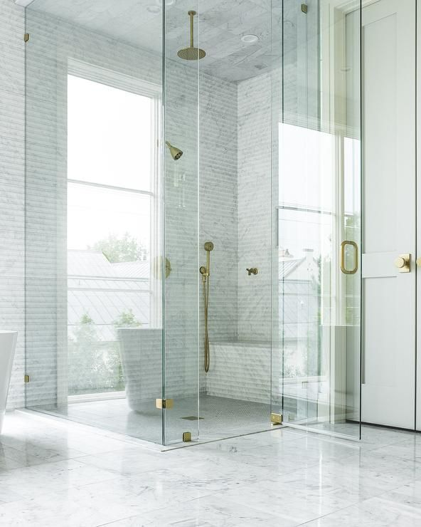 Marble clad floors lead to a gorgeous seamless glass walk in shower ...
