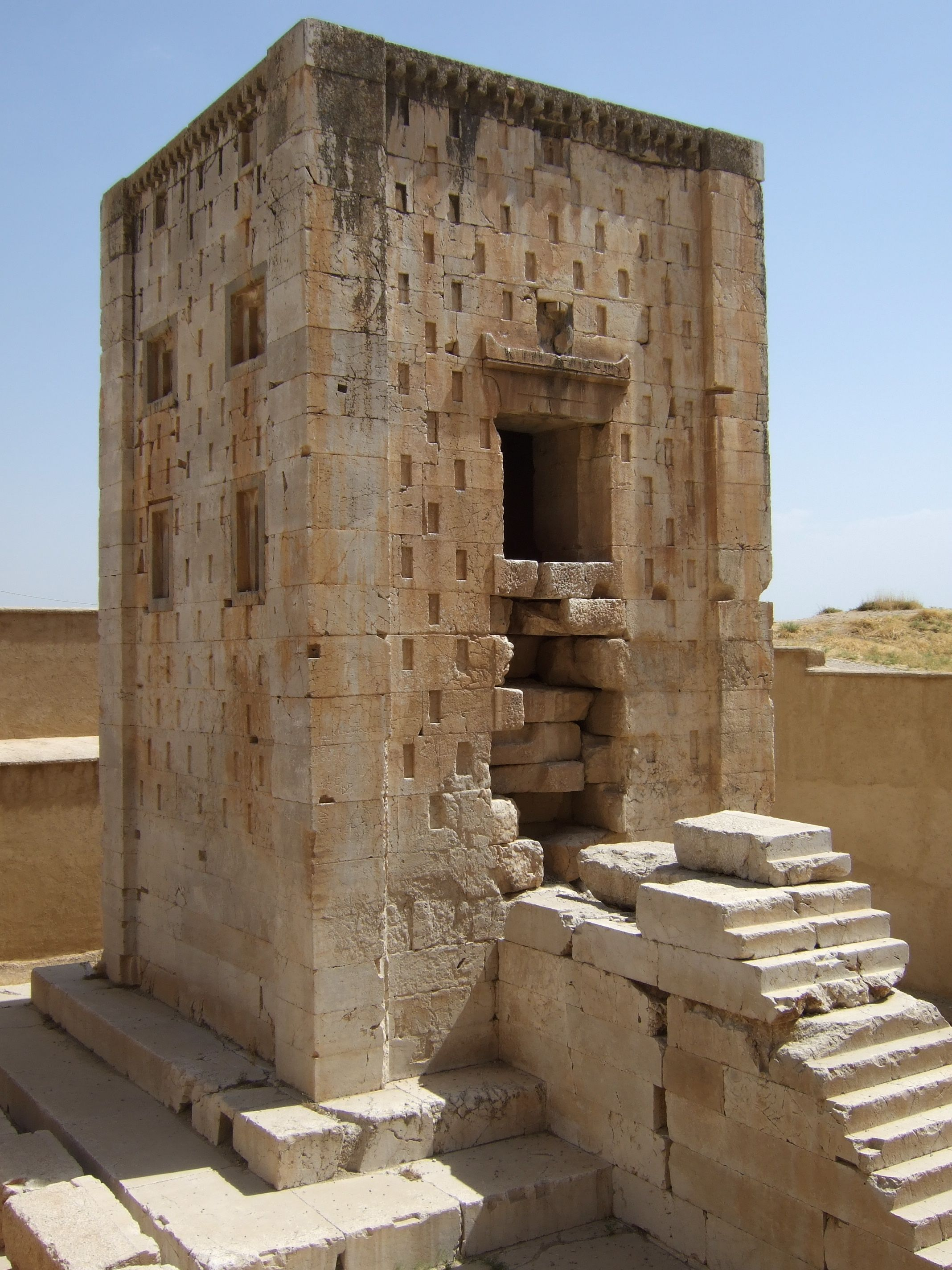 "The Ka'ba-ye Zartosht (""Cube of Zoroaster"") is a 5th century BC Achaemenid-era tower-like construction at Naqsh-e Rustam, northwest of Persepolis, Iran. The name probably dates to the 14th c., when many pre-Islamic sites were identified with figures and events of the Qur'ān or the Shāhnāme. The structure is not actually a Zoroastrian shrine. The structure, which is a copy of a sister building at Pasargadae, was built either by Darius I when he moved to Persepolis, by Artaxerxes II or III."