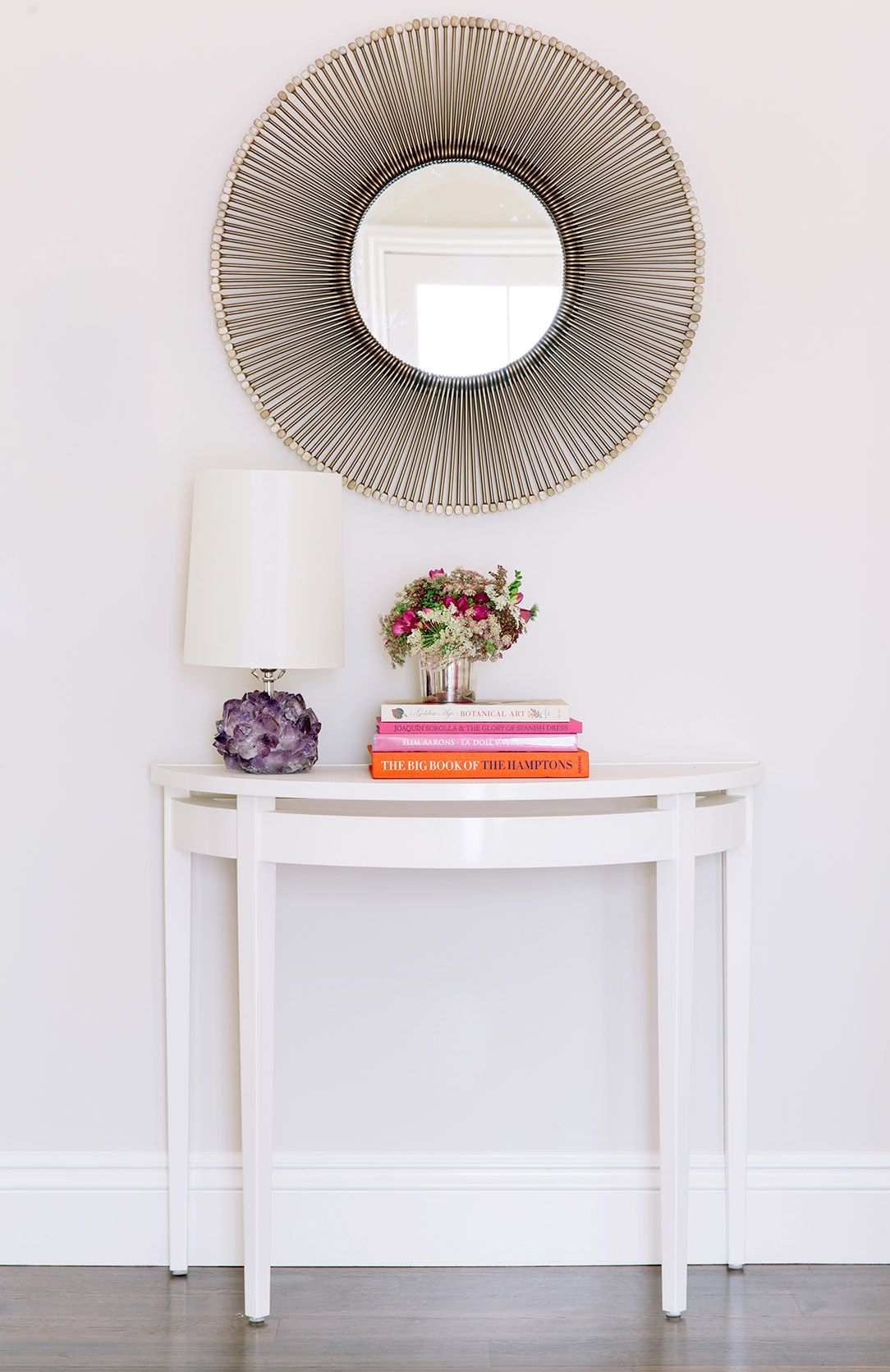 Console table styled with flowers, books, and a lamp and mirror hanging above