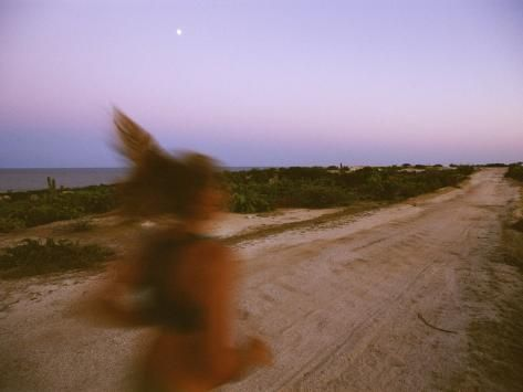 'A Woman Runs Down a Dirt Road in Baja, Mexico at Sunset' Photographic Print - Jimmy Chin | Art.com