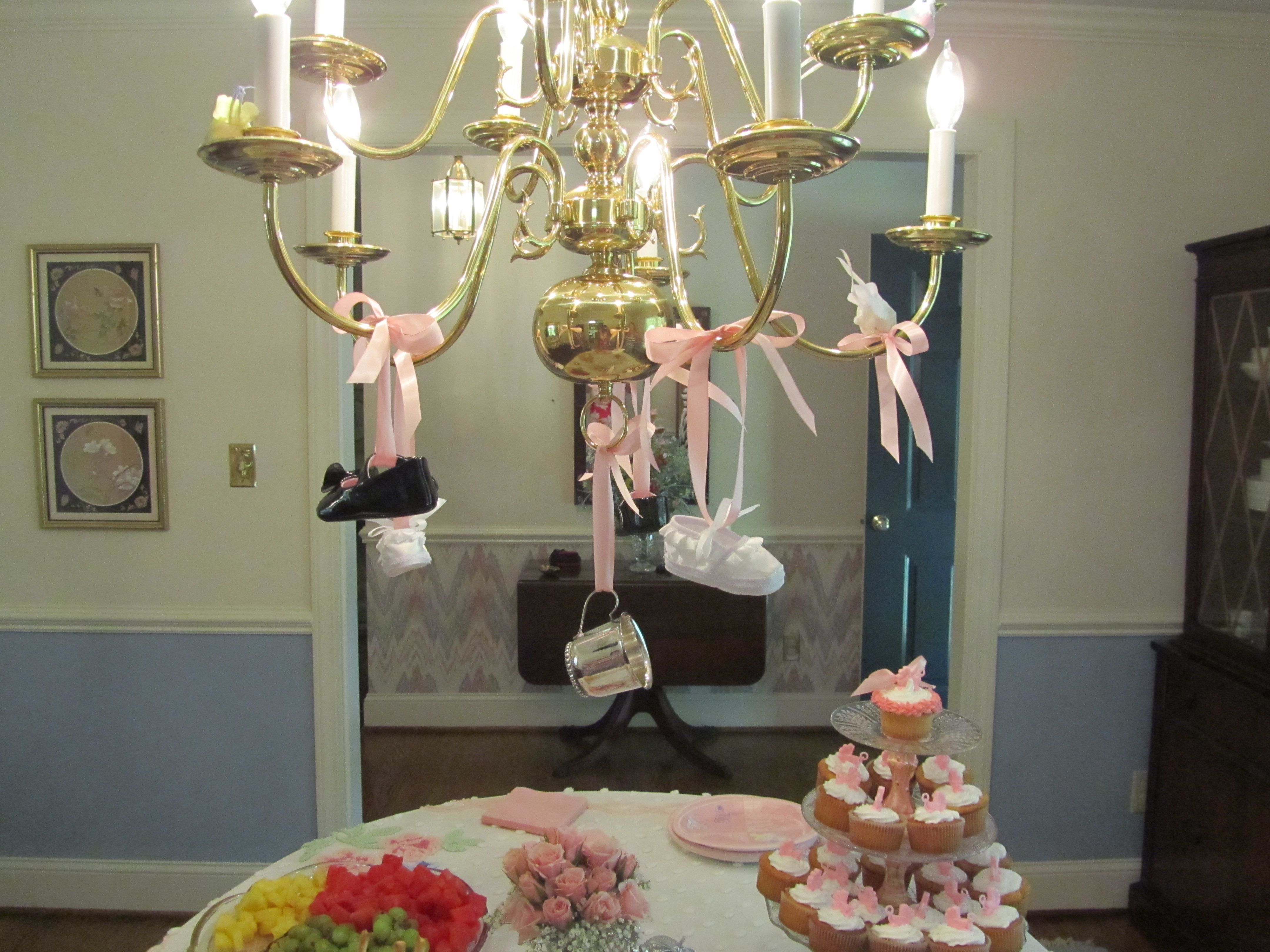 Baby shoes and silver baby cup decorating chandelier
