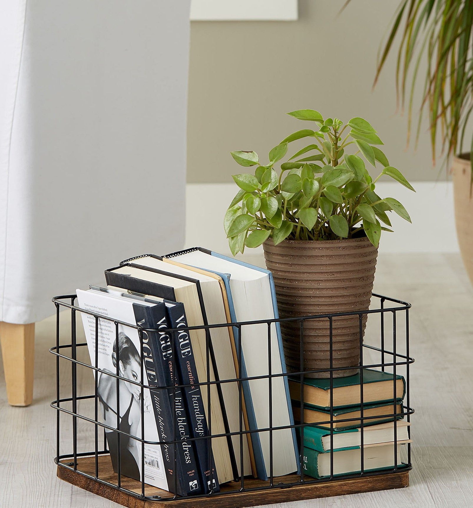 "Photo of A wire metal basket you can use as both storage and decor. The grid pattern in conjunction with the dark solid wood base keeps things simple, without entering ""basic"" territory."