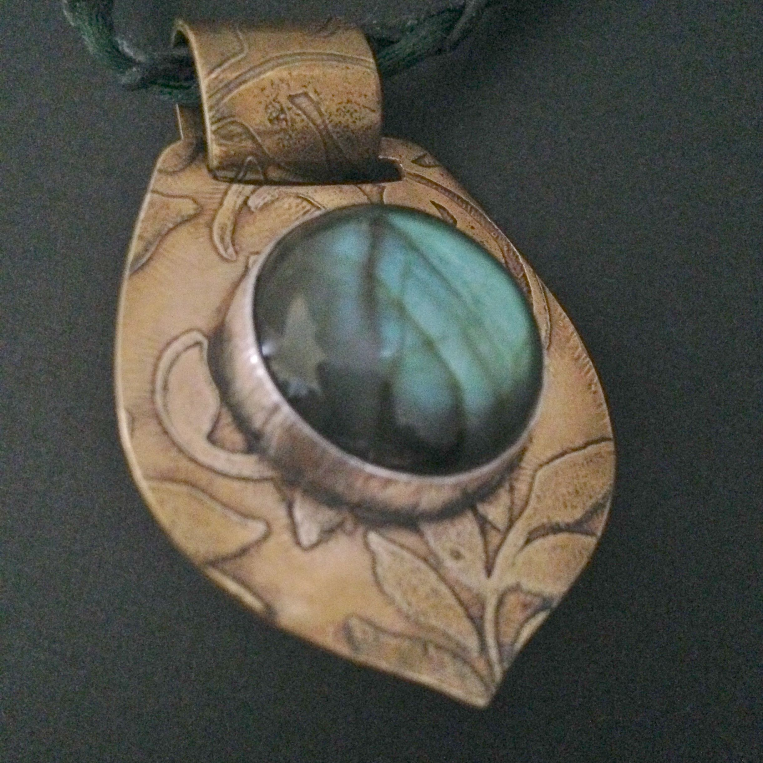 This+beautiful,+flashy+Labradorite+cabachon+is+set+in+a+textured+fine+silver+bezel.++The+brass+back+plate+has+been+etched+and+oxidized+to+bring+out+the+details.++There+is+a+small+heart+shaped+cut+out+on+the+back,+allowing+the+stone+to+show.++It+hangs+from+a+black+leather+cord+that+is+finished+wit...