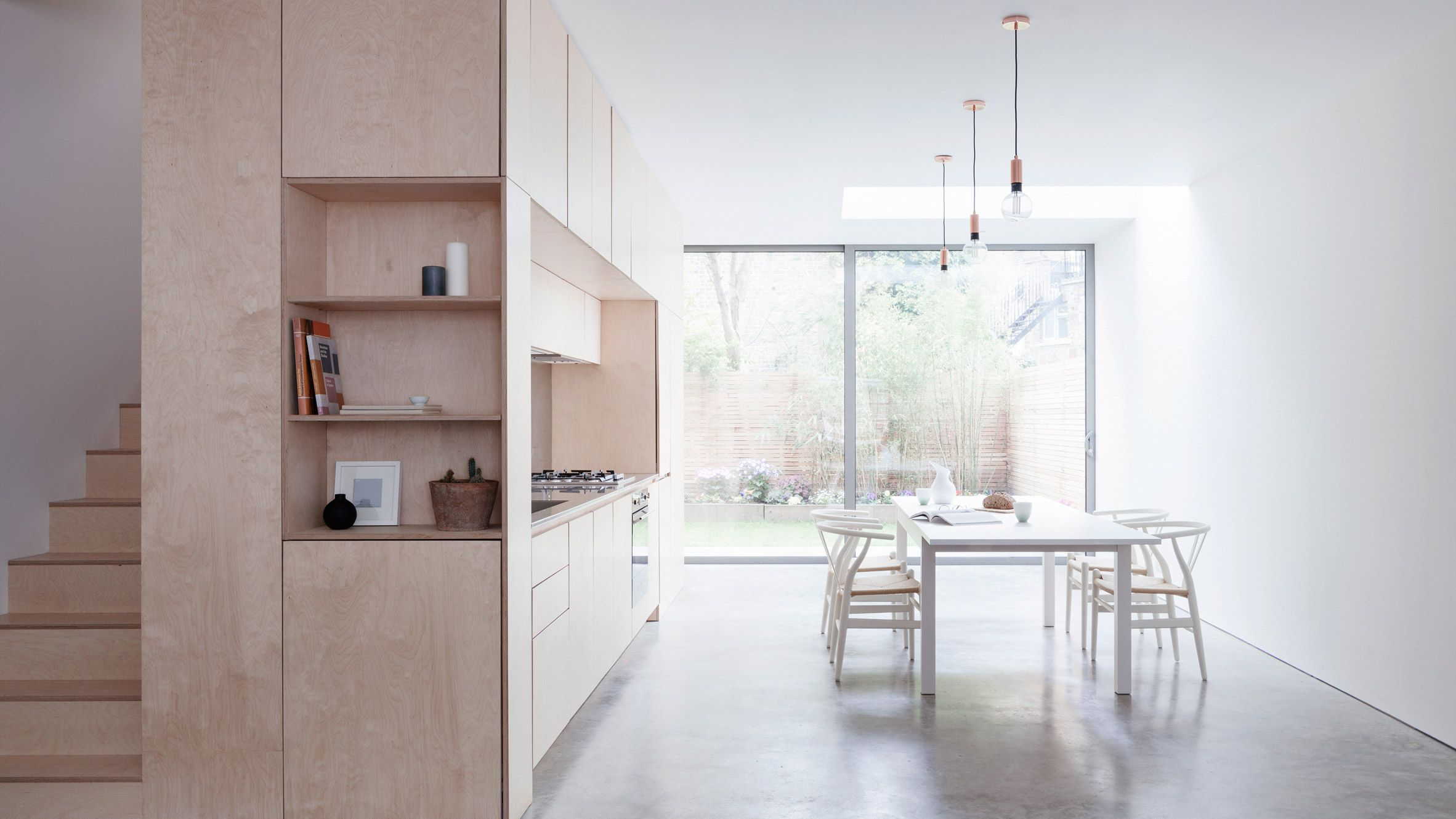 A plywood box hosts the kitchen and staircase in this maisonette in