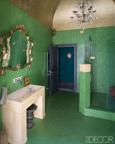 The walls and floor of the master bath are covered in Bisazza tiles, the French mirror is 1950s, and the custom sink was handmade by Sicilian craftsmen; the fittings are by Hansgrohe, and the ceiling is covered in gold leaf.