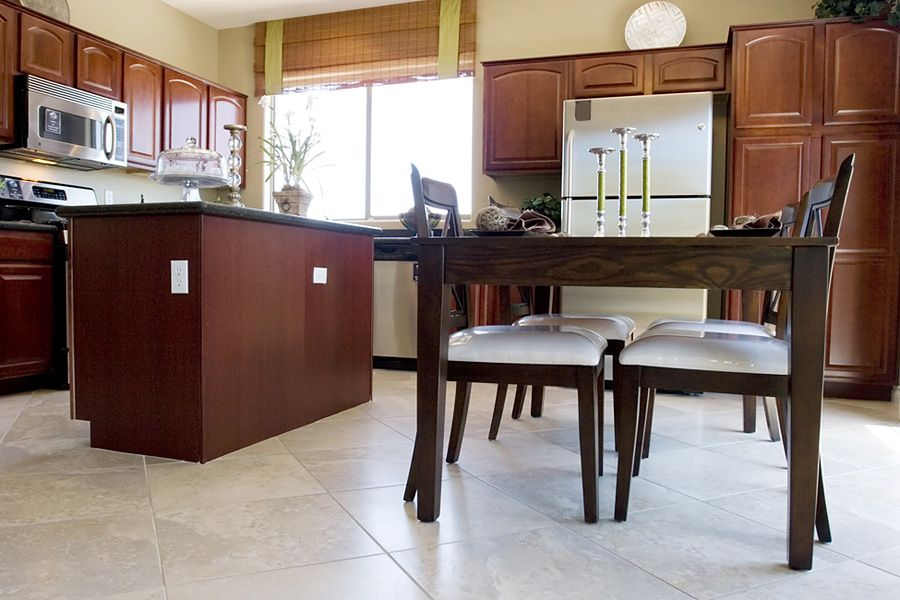 Dark cherry wood cabinets with light ceramic flooring for Perfect tiles for kitchen