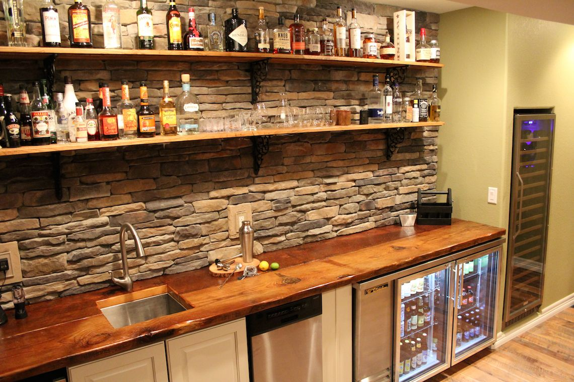 Walk Up Style Wet Bar Featuring Reclaimed Rail Car Floor Planks As Shelves  And Stone Back