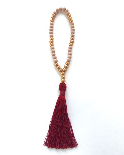 Crimson tassel with blush pink and copper wood beads. Meant to be hung on the rear-view mirror of your car! On stretchy string.
