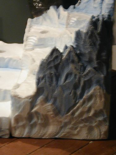 This is a side view of the sculpted North Pole piece showing the carved mountains on the sides and back of the display.