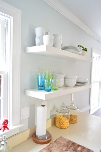 Two Long Ikea Floating Shelves In A Kitchen Holding Colorful Cups And Stacks Of White Dishware Ikea Lack Shelves Ikea Floating Shelves Floating Shelves Kitchen