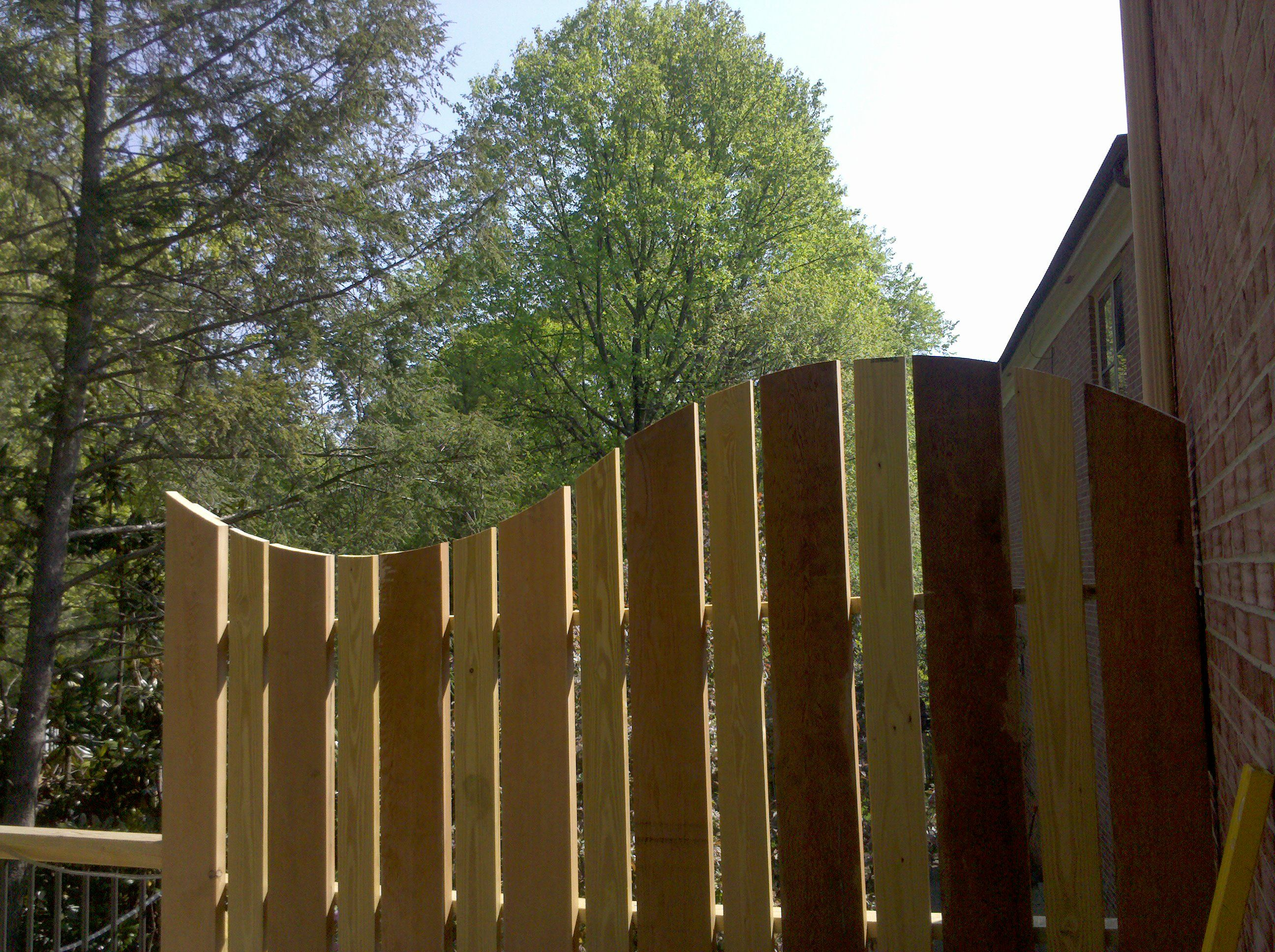 Curve cut into top of privacy wall to block view from neighbor s