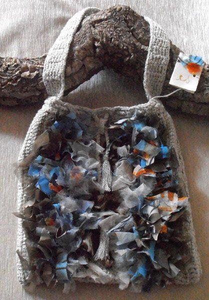 borsa di cotone a tracolla color ecru-ghiaccio, realizzata a uncinetto e decorata con nastri di tessuti pregiati tagliati a vivo e annodati uno ad ...