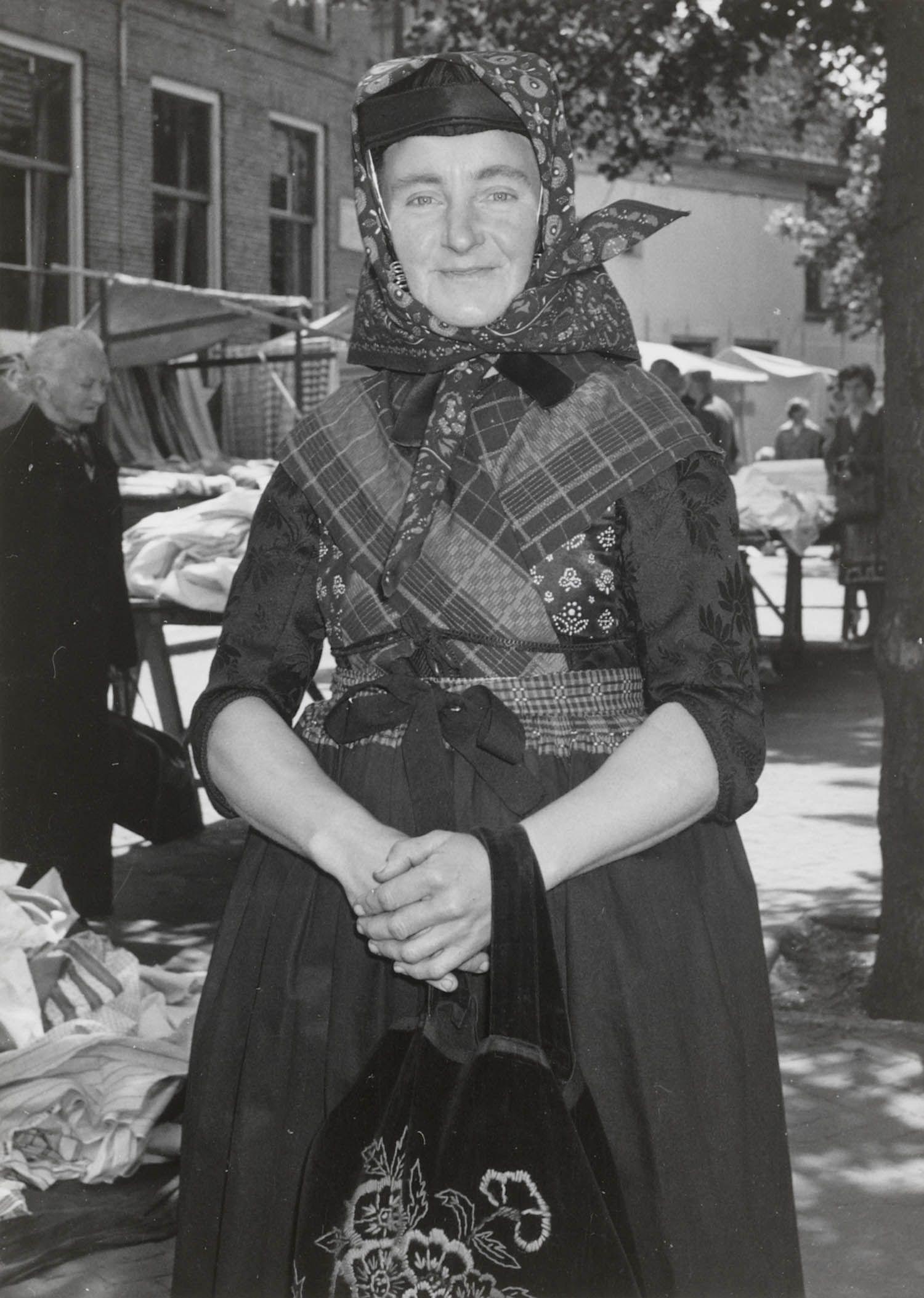 Mevrouw Geesje Konterman-Hooikammer uit Rouveen op de markt te Meppel. Geesje draagt de streekdracht van Staphorst en Rouveen. Ze is gekleed in opknapdracht en is in de zware rouw. Aan haar hand een 'karbies' (tas). Over het oorijzer draagt ze een hoofddoek. 1960 #Overijssel #Staphorst