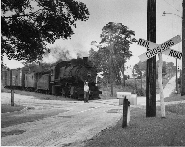 Conductor of Union Transportation Co.s daily train raises his hand in warning to an approaching motorist as 0 6 0 5244, leased from UT parent PRR, eases over a road crossing in Hornerstown, N.J., on 8 28 58.