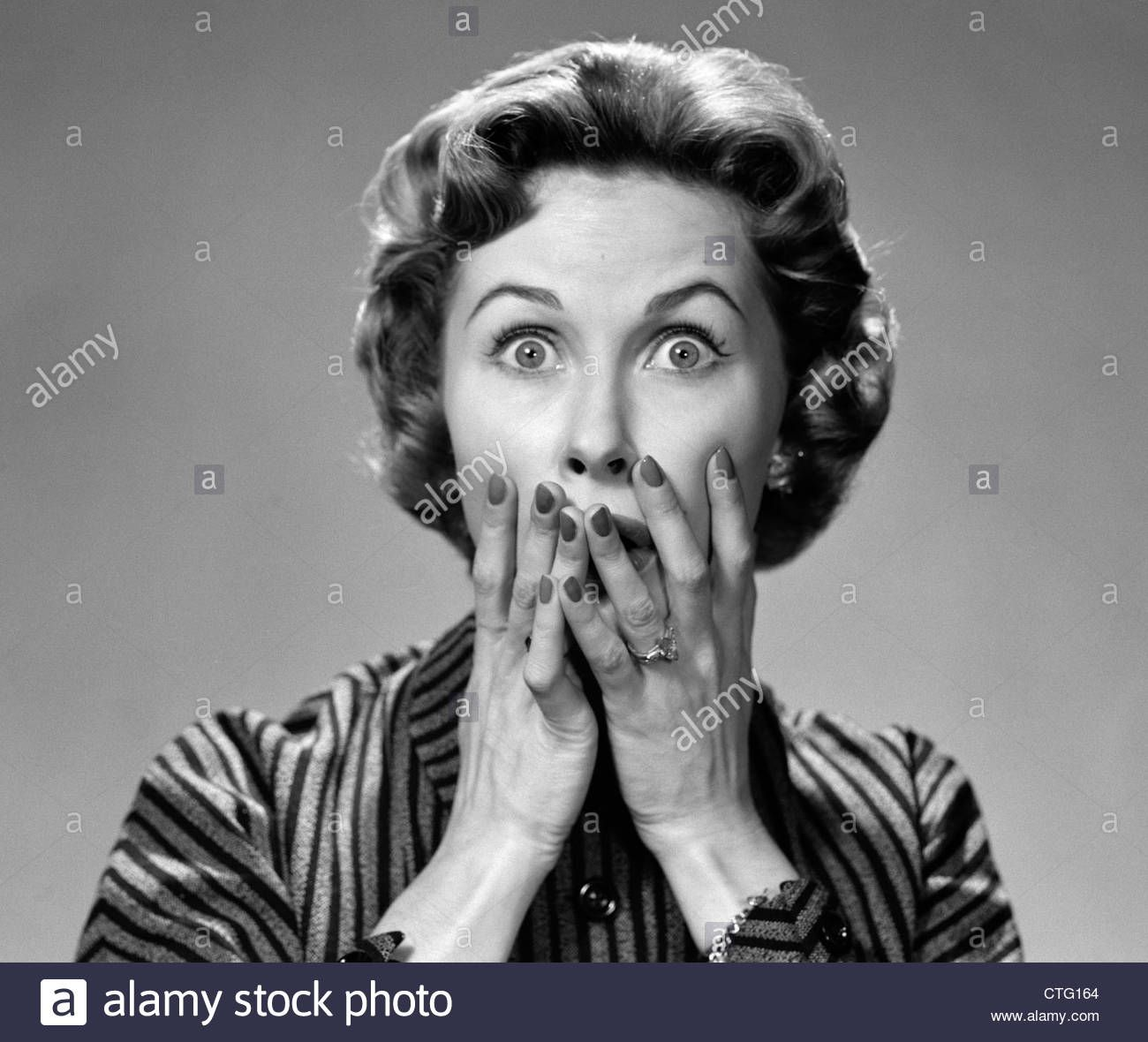 1950s PORTRAIT OF WOMAN IN STRIPED DRESS HANDS TO MOUTH