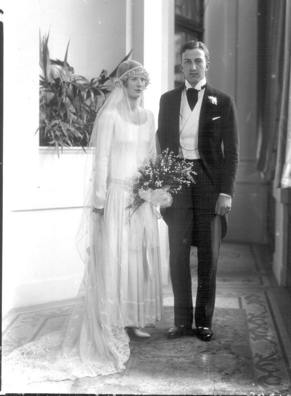 Carrying a charming lily of the valley bouquet Pamela Gladstone married Eustace Gervais Tennyson-d'Eyncourt (doesn't he look dapper in his morning suit and spats?) at St. Margaret's, Westminster on the 1st of June 1926. The bride's wedding dress was apparently a rich cream-colour satin with long sleeves and a quite unusual (for the 1920s!) full skirt. It was finished with a belt of pearl embroideries that beautifully emphasised the fashionably low waist. The train you can glimpse trailing to…