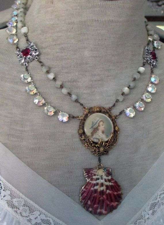 s t o r y: From my vintage beach collection, this show-stopping necklace features a vintage Hobe lithograph portrait pendant of a sweet young girl in blue and white bonnet. I hand wire-wrapped vintage mother of pearl rosary beads and open-back crystal bezel chain to links with red glass stones on each side. Below the pendant, I hung a vintage seashell with gold edging. At the back of the necklace, a vintage rhinestone clasp is surrounded by faceted garnets, with a shell leaf bead dropping…
