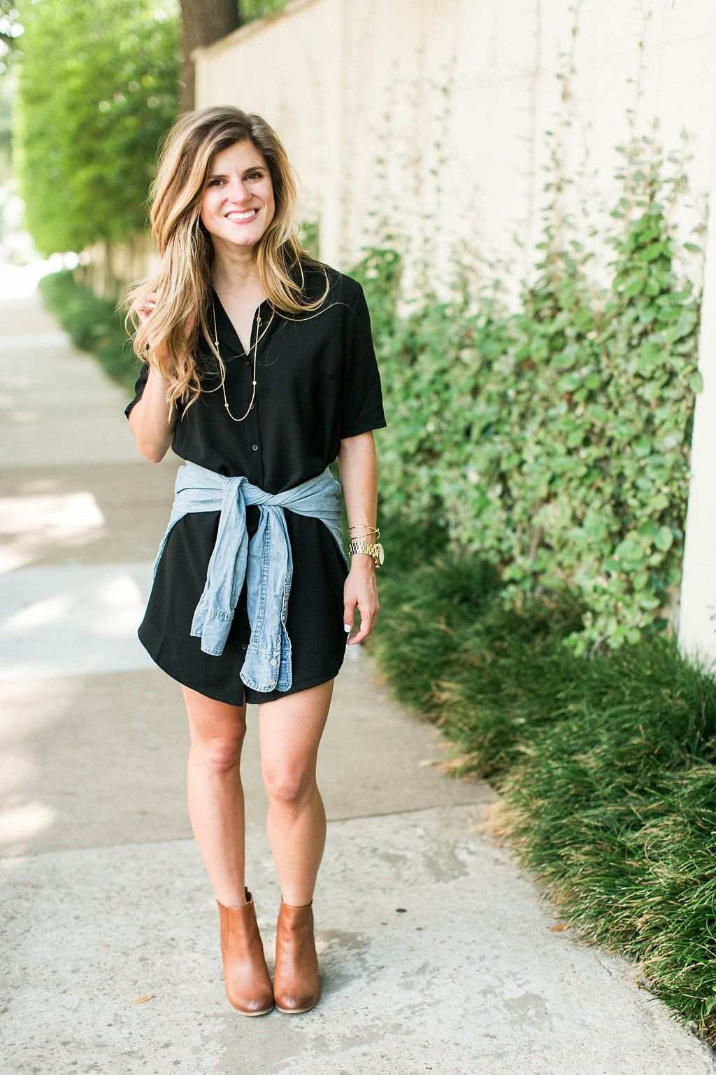 9c3a30a499 brighton keller wearing black shirt dress with chambray tied around waist  and brown booties