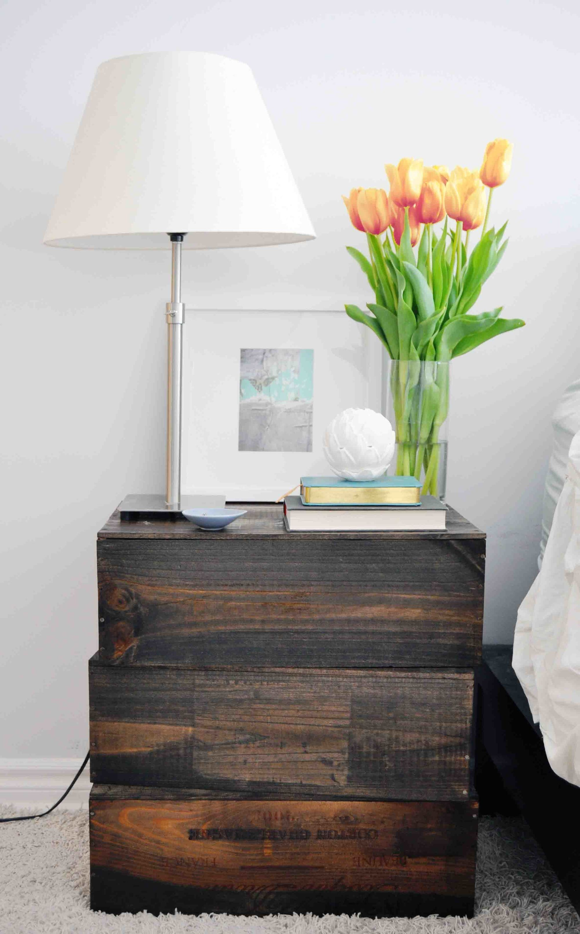 Repurpose old wine boxes into a rustic crate nightstand next to