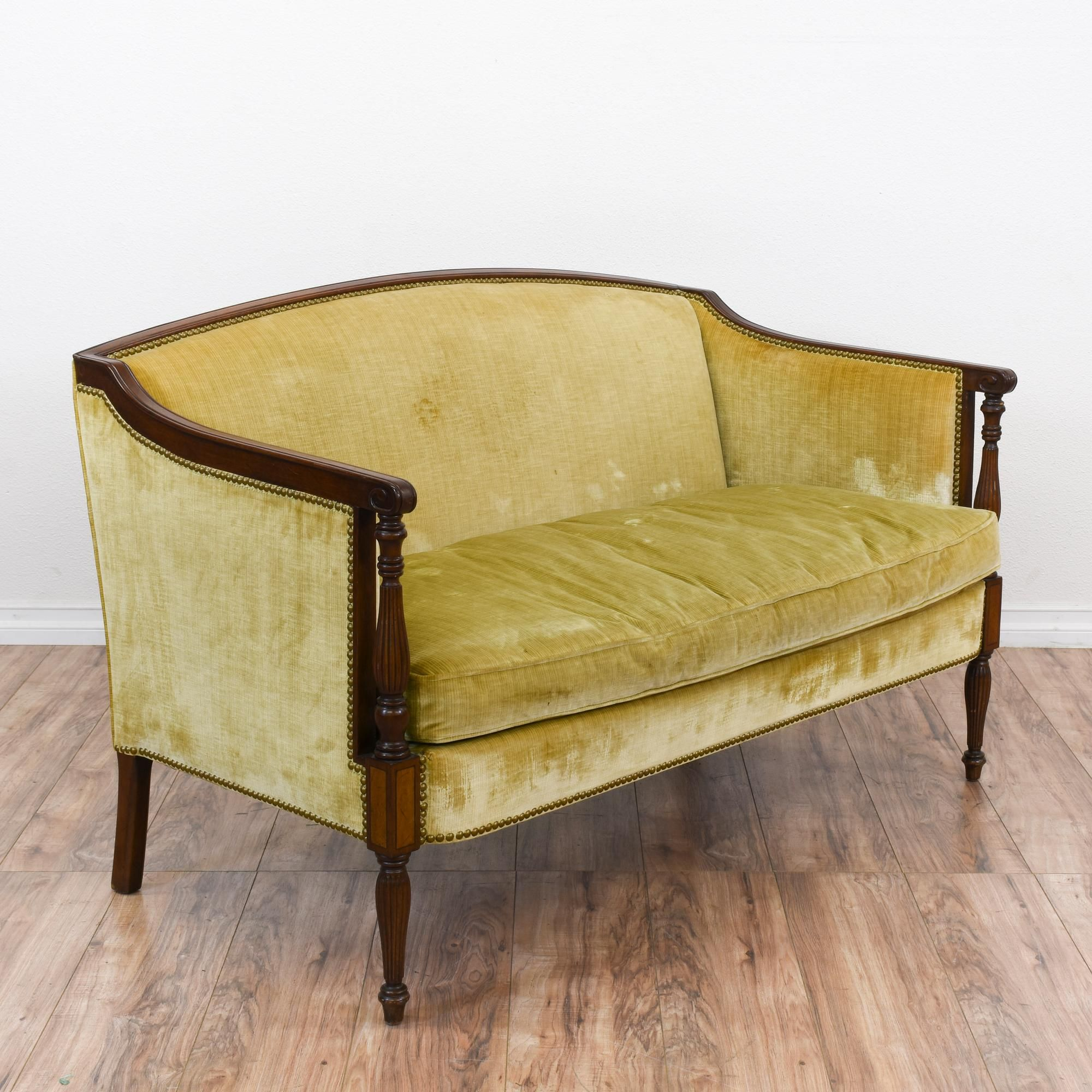This loveseat is upholstered in a durable mustard yellow velvet