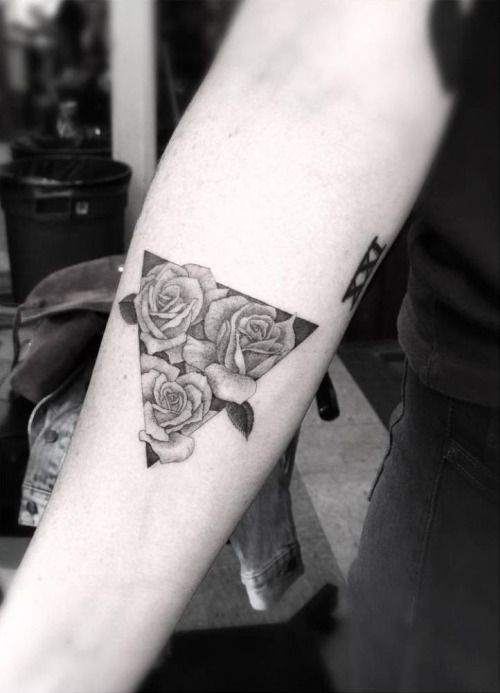 Fine line triangle with three roses on the right inner forearm....