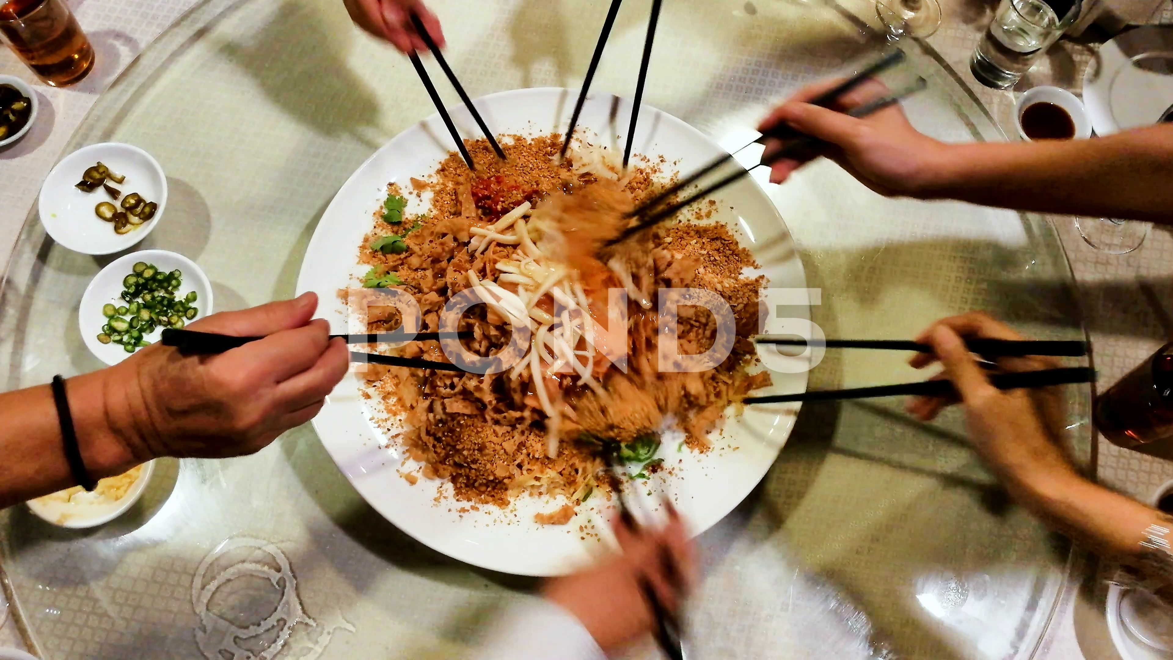 People tossing yee sang or yusheng during Chinese New Year dinner Stock Footage sangyushengyeePeople
