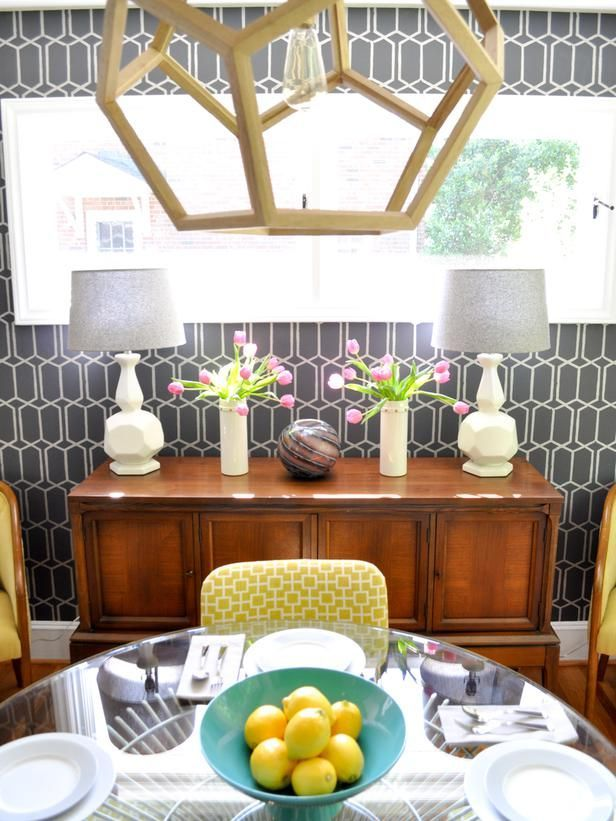 Graphic gray wallpaper adds a layer of dimension to this midcentury modern dining room the geometric pattern is echoed across the yellow dining chairs and